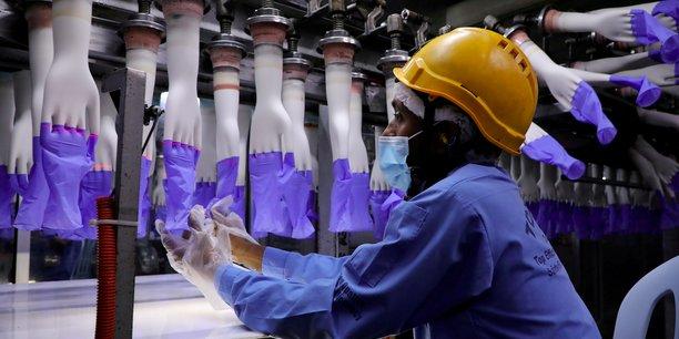 Un travailleur inspecte les gants sur la chaîne de fabrication de l'usine Top Glove de Shah Alam, en Malaisie, le 26 août 2020.
