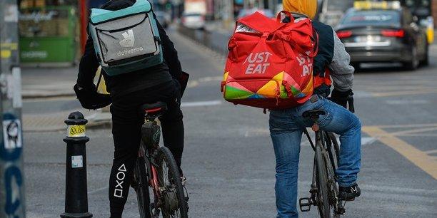 Des livreurs à vélo travaillant pour des plateformes numériques telles Deliveroo ou Just Eat, s'apprêtent à livrer une commande.