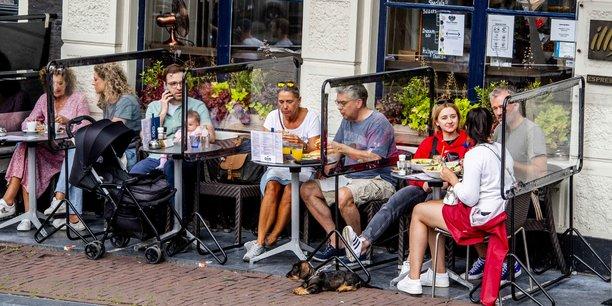 Photo d'illustration: à Amsterdam, en juin 2020, une terrasse de restaurant équipée de cloisons en plexiglas anti-Covid.