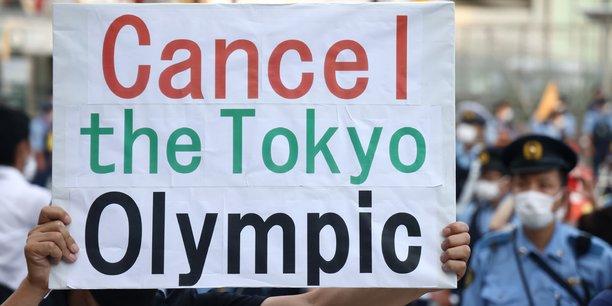 Des manifestants protestent le 23 juillet à Tokyo, jour d'ouverture des JO 2020,  à l'entrée du stade olympique.