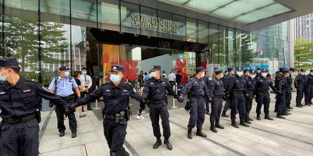 Le siège du géant chinois de l'immobilier Evergrande Real Estate Group défendu par un cordon de policiers face à des dizaines de propriétaires spoliés qui manifestent.