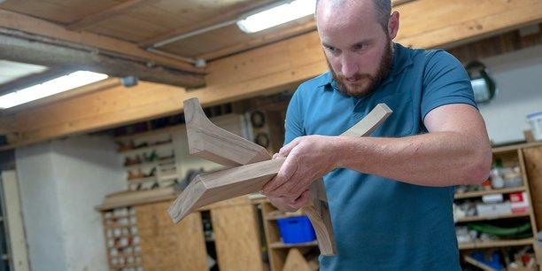 L'entrepreneur ébéniste Hugo Delavelle évalue l'assemblage du pied tulipe tripode d'une de ses dernières créations.