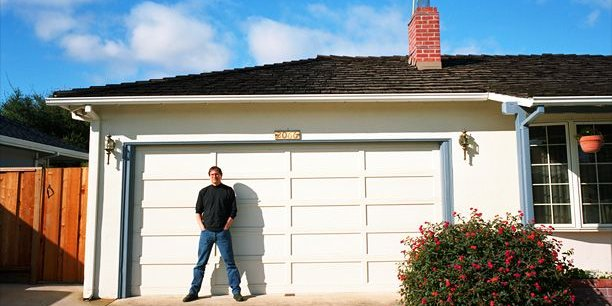 Steve Jobs pose en 1996 devant la porte du garage où il a créé son premier ordinateur, à Los Altos en Californie. (Photo Cook - Jensen pour Reuters)