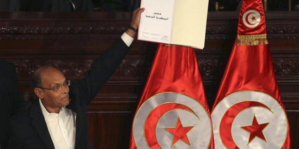 La signature de la Constitution tunisienne en février 2014, ici par le Président Marzouki, éloigne le spectre de l'instabilité politique. L'économie va pouvoir prendre toute sa place.