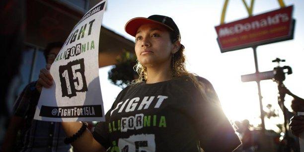 Cette manifestante en Californie brandit un panneau en faveur du salaire minimum à 15 dollars. (Photo: Reuters)