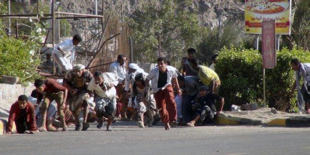 Des civiles cherchent à s'abriter lors d'une attaque dans la base militaire de la ville d'Aden, le 25 mars.