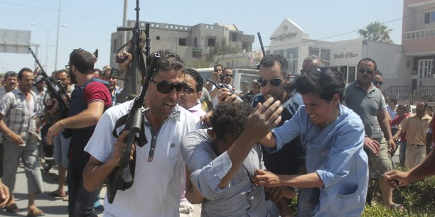 Les policiers tunisiens embarquent un homme suspecté d'être un des hauteurs de l'attentat.