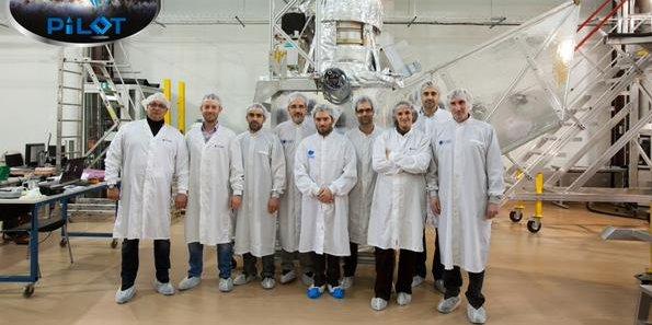 Une partie de l'équipe de Pilot devant la nacelle qui contient l'instrument de la mission
