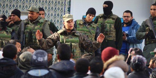 Un soldat de l'armée tunisienne tente de disperser les manifestants massés devant les locaux de la préfecture de Kasserine, point de départ de la contestation.