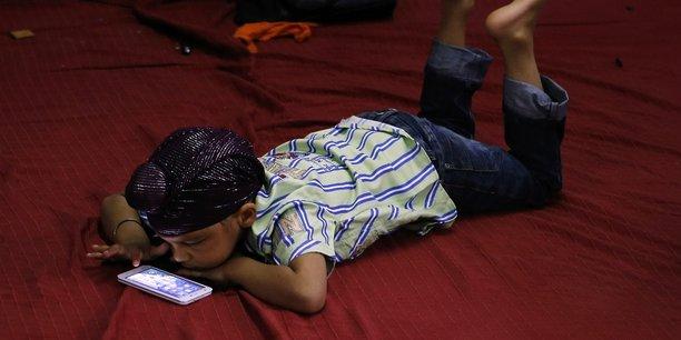 Un jeune Sikh joue sur son smartphone dans un temple indien.