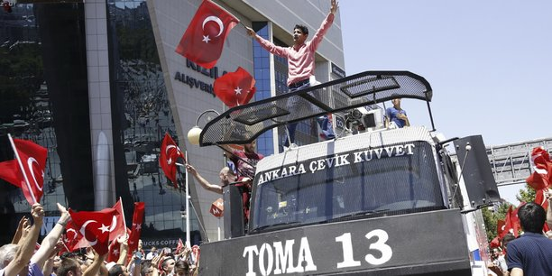 Des partisans du président Recep Tayyip Erdogan célèbrent l'échec du coup d'Etat autour d'une voiture de Police à Ankara, samedi 16 juillet.