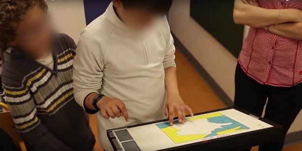 De jeunes déficients visuels testent la carte en relief posée sur un écran tactile.