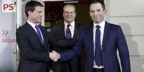 Manuel Valls et Benoît Hamon, se congratulant au siège du PS le 29 janvier, sous les yeux du Premier secrétaire, Jean-Christophe Cambadélis