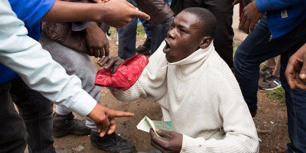 Un homme brandissant ces papiers d'identité sud-africains pour éviter le lynchage de la foule, lors d'une manifestation xénophobe à Pretoria le 24 février dernier.