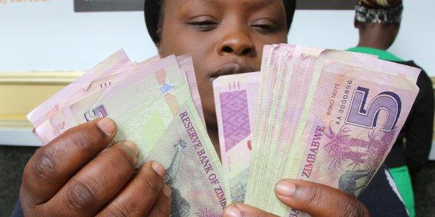 Un courtier en devises compte des billets d'obligations à l'extérieur d'une banque à Harare