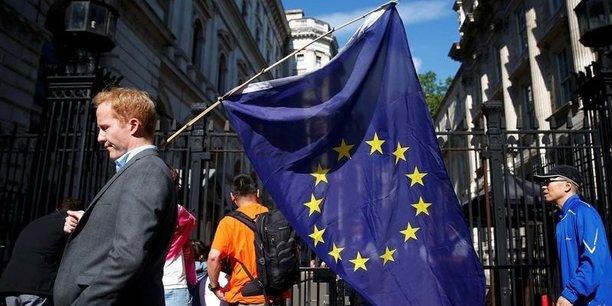 Un homme portant un drapeau européen passe devant Downing Street, à Londres.