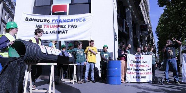 La veille des AG, des militants d'ONG, dont les Amis de la Terre, ont organisé un happening devant une agence de la Société Générale à Paris, contre le financement de projets d'oléoduc ou de gaz naturel liquéfié affectant les populations autochtones.
