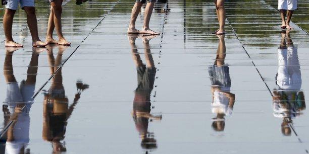 Lors de la vague de chaleur qui a déferlé sur la France en juin 2015, des citadins se rafraichissent sur le Miroir d'eau du quai de la Garonne, à Bordeaux.