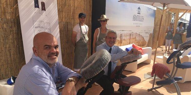 Hervé Maudet et Jean Merlaut, propriétaires d'Abatilles, sur leur stand à Vinexpo, dédié à la promotion de leurs bouteilles grand cru.
