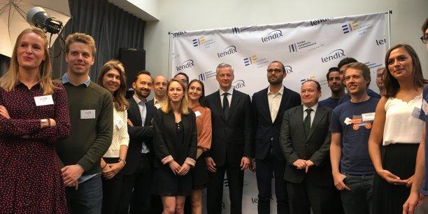 Le ministre Bruno Le Maire, aux côtés d'Olivier Goy, le fondateur et président de Lendix, et d'Ambroise Fayolle, vice-président de la Banque européenne d'investissement (BEI), entourés des équipes de la plateforme de prêts participatifs aux PME au siège de Lendix à Paris ce lundi.