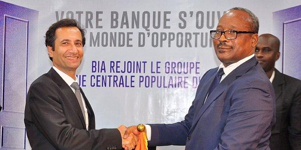 Poignée de main symbolique entre Mohamed Benchaaboun, PDG du Groupe marocain BCP, et Muhamadu Issoufou, président du Niger, scellant la transaction autour de BIA-Niger.