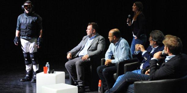 Les participants de la 2e table-ronde accueillent un démonstrateur de l'exosquelette, simulant les effets du viellissement, conçu par l'I2ML de Nîmes