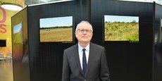 Michel Duchène pose devant des clichés représentant des paysages de Bordeaux Métropole.