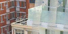 La nouvelle version du bâtiment de couleur blanche et bardée de métal tissé, se démarque de l'immeuble en brique en arrière-plan, où dominent la pierre, le zinc et les tuiles.