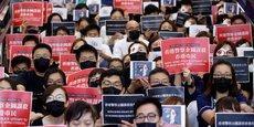 Mardi 13 août 2019, le piquet de grève du personnel médical de l'hôpital Queen Elizabeth de Hong Kong qui proteste avec des pancartes dénonçant les violences policières lors de récentes manifestations antigouvernementales. Quelques manifestants portent de faux pansements sur un oeil pour illustrer le slogan oeil pour oeil (lire détail en pied d'article).