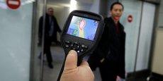 Le 21 janvier 2020, à l'aéroport international, un employé des services sanitaires et épidémiologiques kazakh utilise un scanner thermique pour détecter les voyageurs en provenance de Chine à leur arrivée au Kazakhstan qui pourraient présenter des symptômes liés au nouveau coronavirus chinois .
