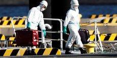 Des agents en équipements de protection sur le port de Yokohama, au sud de Tokyo (Japon), le 5 février se rendent auprès des passagers du bateau de croisière Diamond Princess où quelque dix touristes ont été déclarés contaminés par le coronavirus.