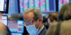 Un trader avec son masque de protection au New York Stock Exchange. Un accord sur un plan de relance de 2.000 milliards de dollars a été annoncé par le chef de la majorité républicaine au Sénat américain afin de relancer l'activité.