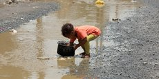 Yémen : un enfant nettoie une marmite avec de l'eau de pluie dans un bidonville de la capitale Sanaa, le 26 juillet 2020.