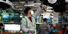 Photo prise le 6 mai 2020 à l'intérieur de l'usine Renault de Flins (menacée par l'actuel plan de restructuration): un ouvrier avec masque chirurgical travaille sur la chaîne de montage des Renault Zoe, le constructeur automobile ayant relancé sa production après la mise en place de mesures de protection anti-Covid.