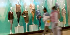 Shoppers walk past a window display of mannequins at the Christiana Mall in Newark
