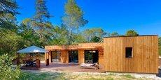 Une maison à ossature bois et son terrain en bordure de forêt.