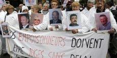 Des manifestants brandissent des photographies de morts présumés à cause de l'amiante lors d'une manifestation à Paris le 6 novembre 2013.