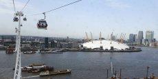 A Londres, un téléphérique urbain enjambe la Tamise pour relier le quartier de Greenwich et  l'O2 Arena (visible au fond avec son dôme blanc hérissé de pilônes de soutènement).