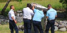 Les gendarmes soulèvent le débris d'avion. Ils doivent mener des expertises afin de déterminer s'il appartient au vol MH370 de la Malaysian Airlines.