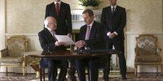 Le président irlandais Michael O'Higgins (à gauche) signe le décret de dissolution du parlement et le remet au premier ministre Enda Kenny (à droite).