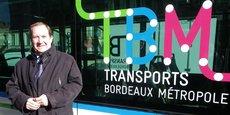 Christophe Duprat devant le nouveau logo sur un bus de la liane 1+