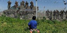 Un enfant regarde les soldats macédoniens postés à la frontière de la Grèce, tout près du camp de migrants d'Idomeni.