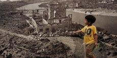 Un enfant japonais passe devant une photographie de la ville d'Hiroshima après le bombardement, lors d'une exposition au Musée du mémorial de la paix d'Hiroshima.