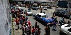 Sur la photo, à Caracas, le 15 juillet, des gens font la queue pour s'approvisionner en produits de première nécessité dans un marché municipal.