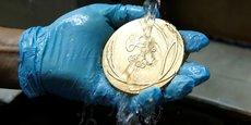 Un employé de l'usine de fabrication des médailles des JO 2016 de Rio nettoie une médaille d'or.