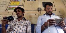 Des voyageurs indiens consultent leurs smartphones dans un train de banlieue de Mumbai.