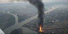 Une épaisse colonne de fumée noire qui s'éleve au dessus du port fluvial de la ville.