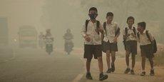 Des écoliers indonésiens marchent le long d'une route polluée (septembre 2016).