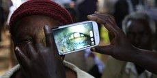 Une femme subit un examen oculaire à l'aide d'un smartphone dans une clinique temporaire du Centre international pour la santé oculaire à Olenguruone au Kenya