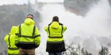 Le personnel du Service des eaux de Californie surveille l'évolution de la situation depuis les hauteurs en face du barrage hydroélectrique, le plus haut ouvrage du genre des Etats-Unis.